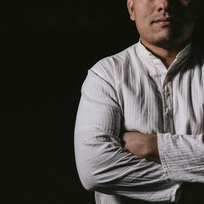 「暗闇の中、立ちはだかる男性」の写真素材