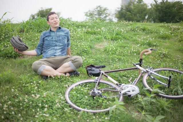 目的地についてくつろぐ自転車男子の写真