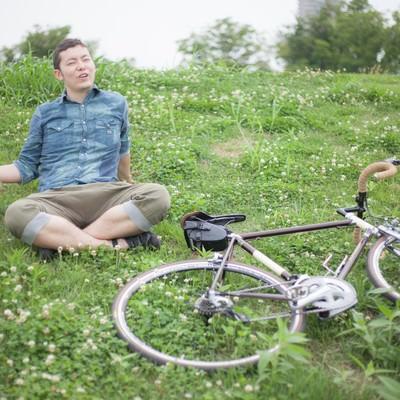「目的地についてくつろぐ自転車男子」の写真素材