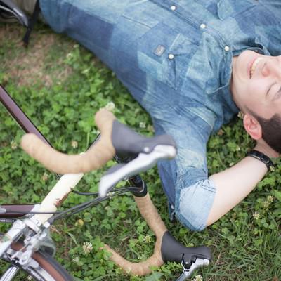 デッドヒートを避け休憩する自転車男子の写真