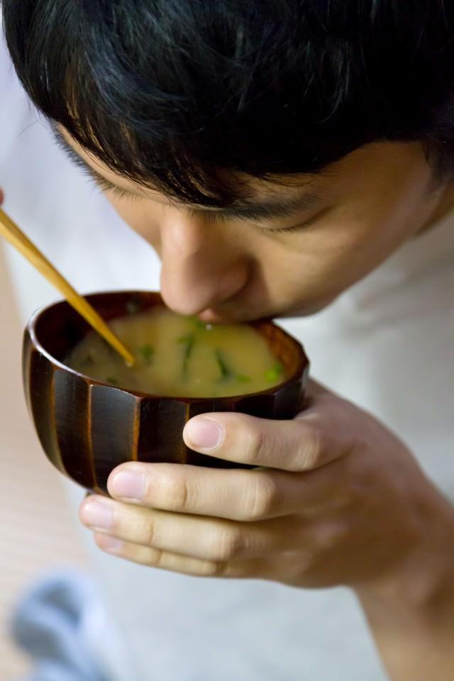 味噌汁をすする男性の写真