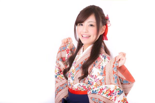 着物の袖を持った笑顔の成人女性の写真
