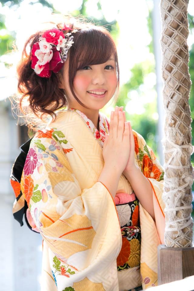 初詣で願いごとをする振袖の女性の写真