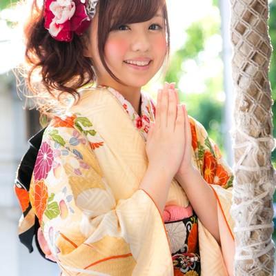 「初詣で願いごとをする振袖の女性」の写真素材