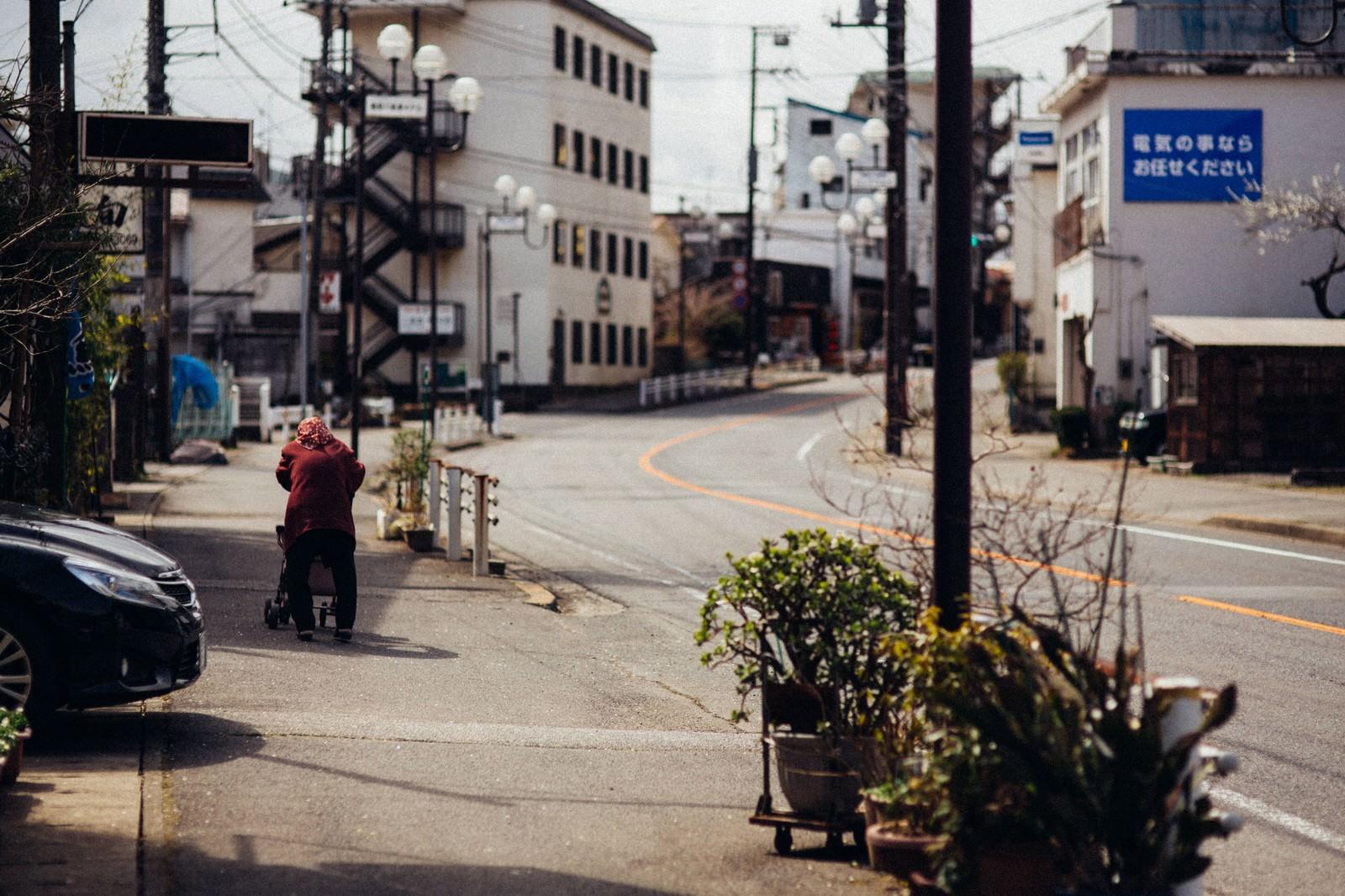 「閑散とした街と老婆の後ろ姿」の写真