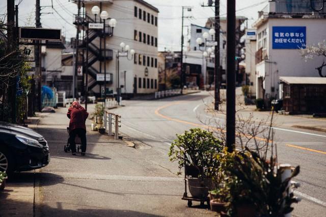 閑散とした街と老婆の後ろ姿の写真