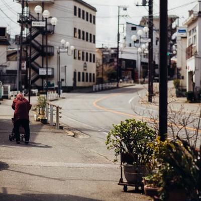 「閑散とした街と老婆の後ろ姿」の写真素材