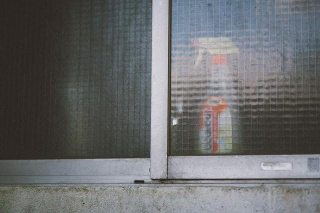 「老朽化したアパートの窓と洗剤」のフリー写真素材