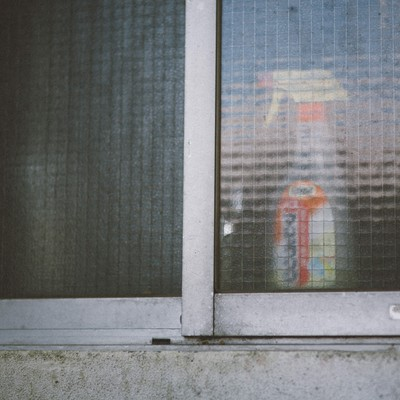 老朽化したアパートの窓と洗剤の写真