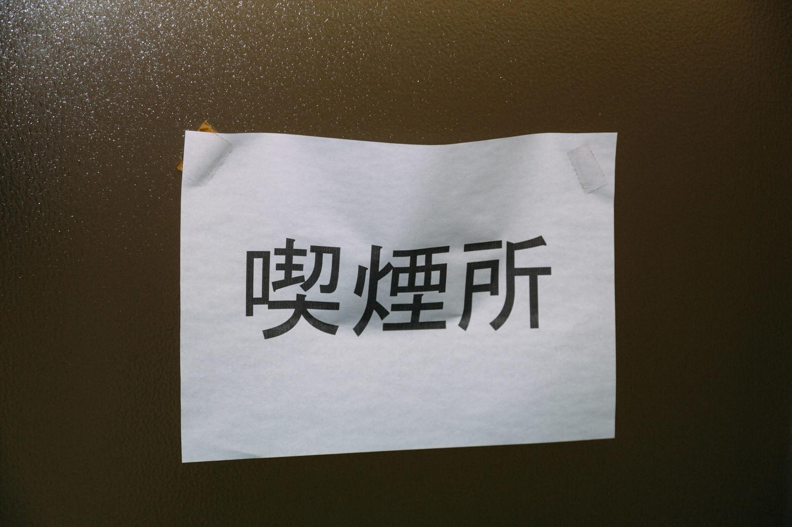 「A4のコピー用紙で貼られた喫煙所」の写真