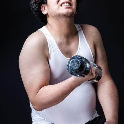 シックスパックだった時代を思い出しながらトレーニングに励む会社員の写真