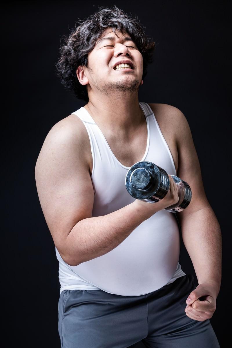 「シックスパックだった時代を思い出しながらトレーニングに励む会社員」の写真[モデル:朽木誠一郎]
