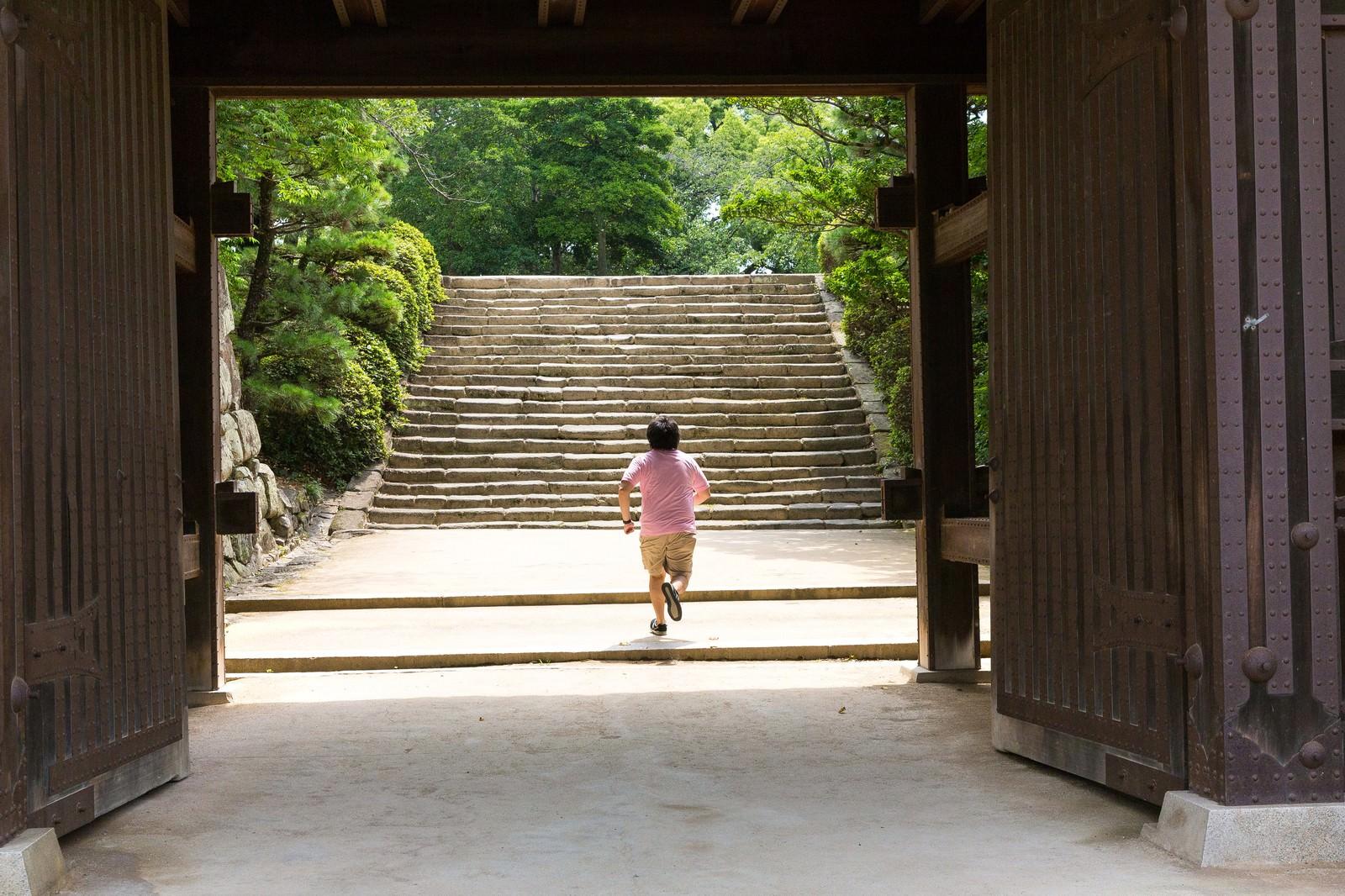 「城門(岡山城)を撮影中、走りだすAD   写真の無料素材・フリー素材 - ぱくたそ」の写真[モデル:朽木誠一郎]