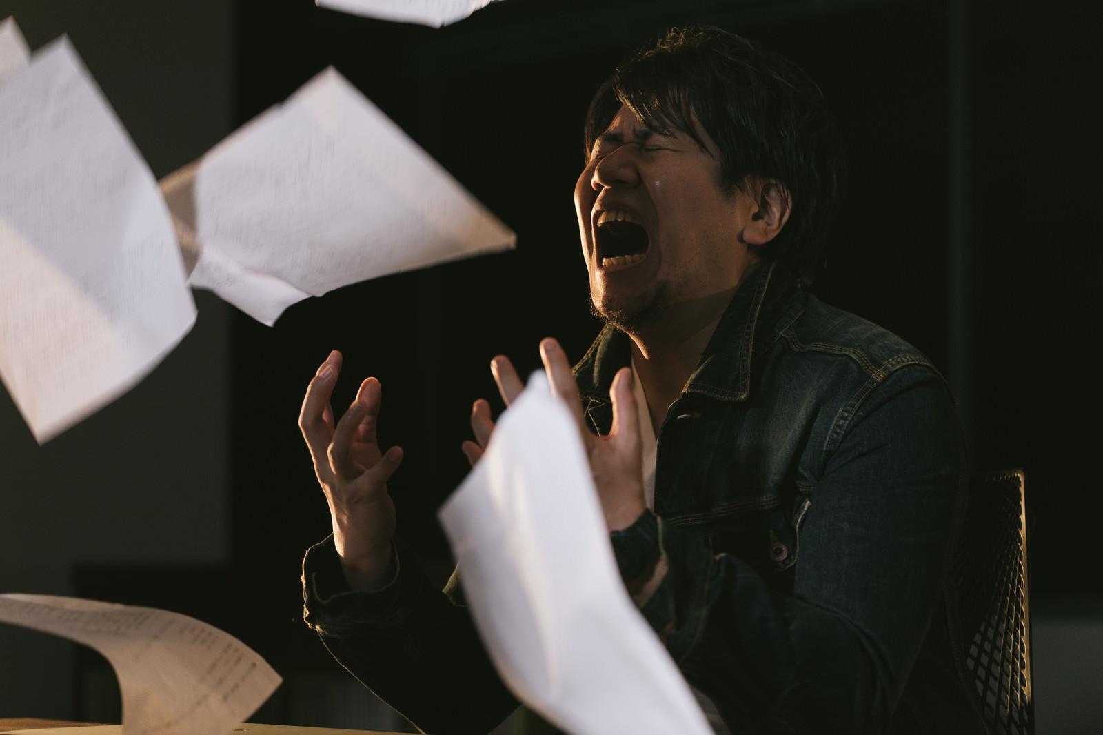 「締切間に合わず原稿を投げ捨てる記者」の写真[モデル:朽木誠一郎]