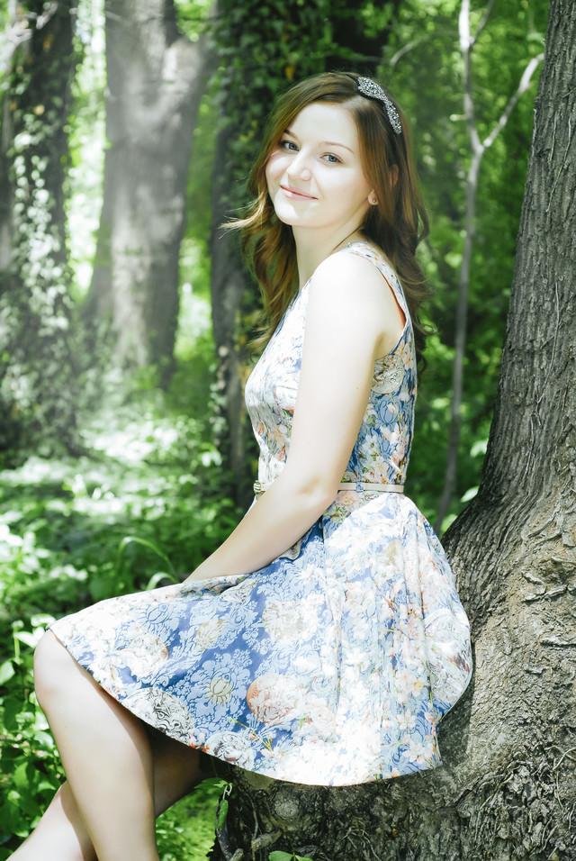 森の中で木によりかかる外国人女性の写真