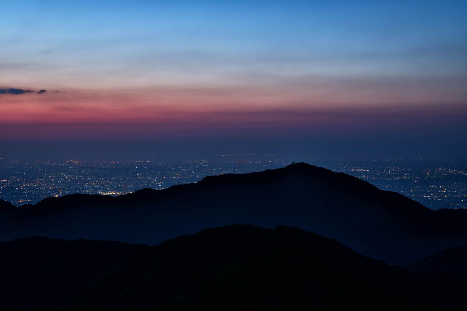 「大山のシルエットと眼下に広がる街の夜景」の写真