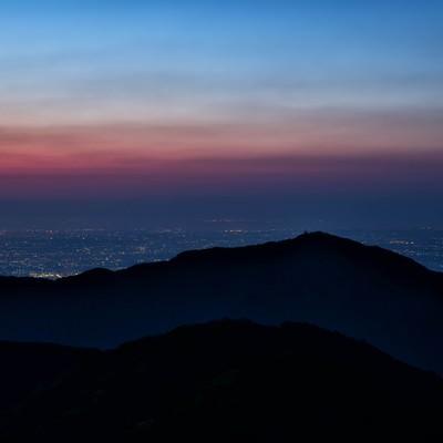 大山のシルエットと眼下に広がる街の夜景の写真