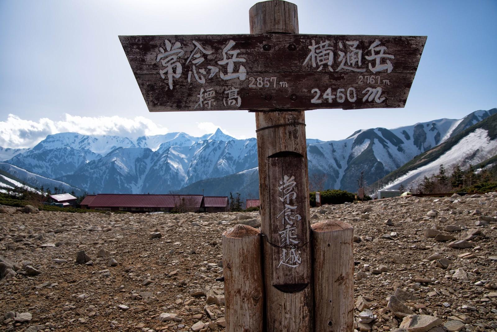 「常念乗越の看板と山小屋から望む山峰」の写真