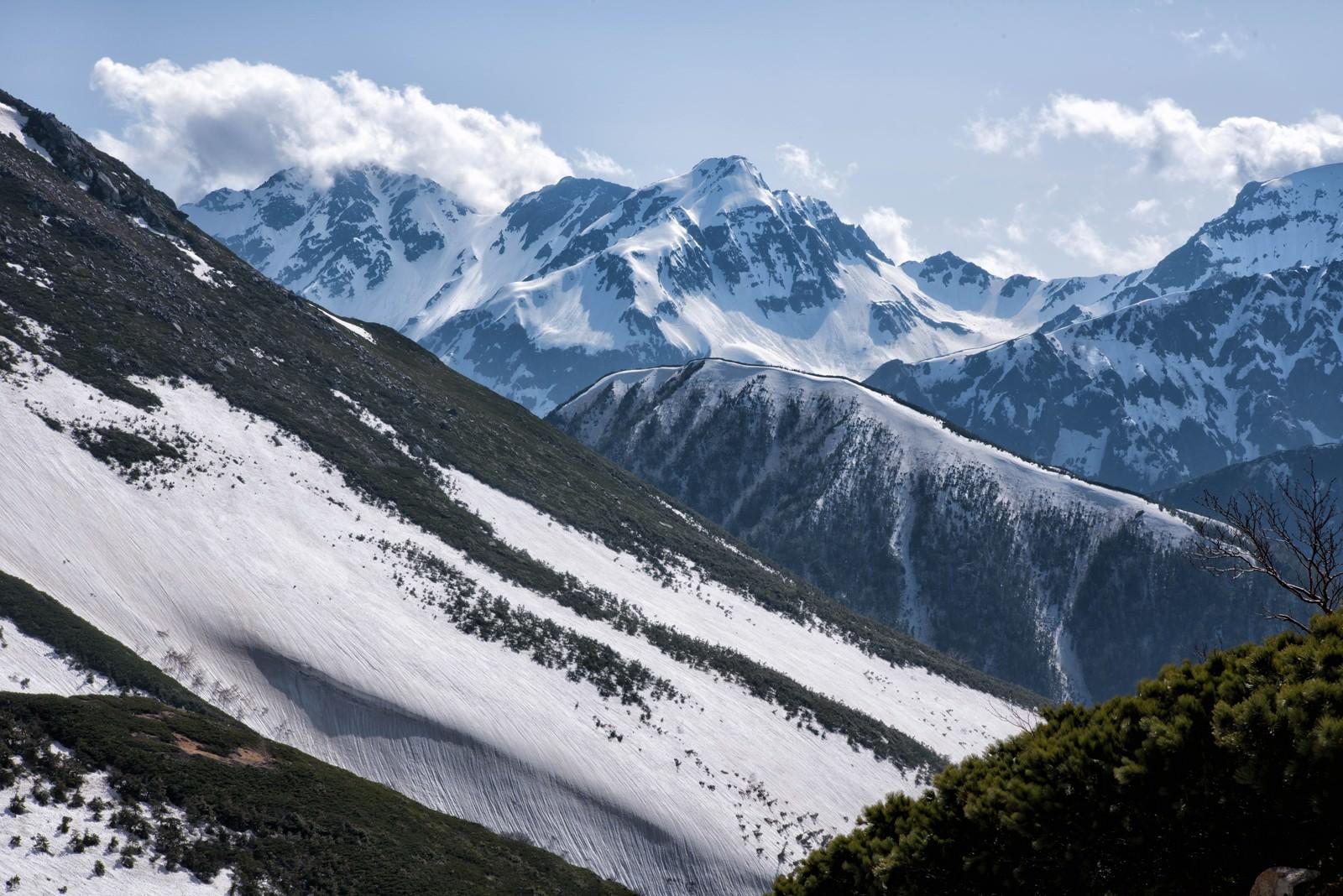 「常念山脈から望む沸き立つ雲と北穂高岳」の写真