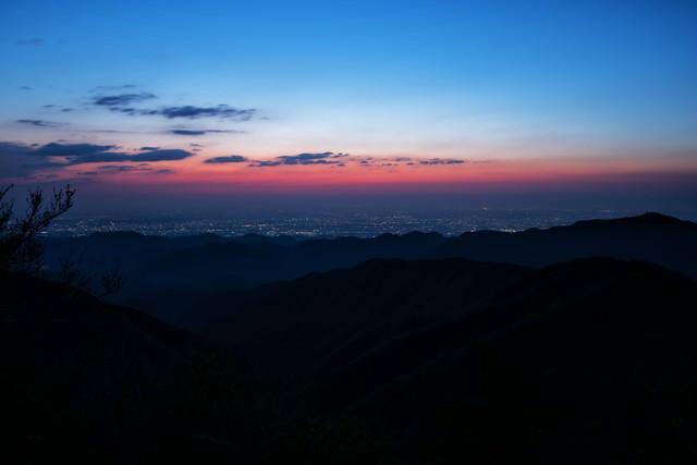 茜色に染まる空と街並みを望む山々のシルエットの写真