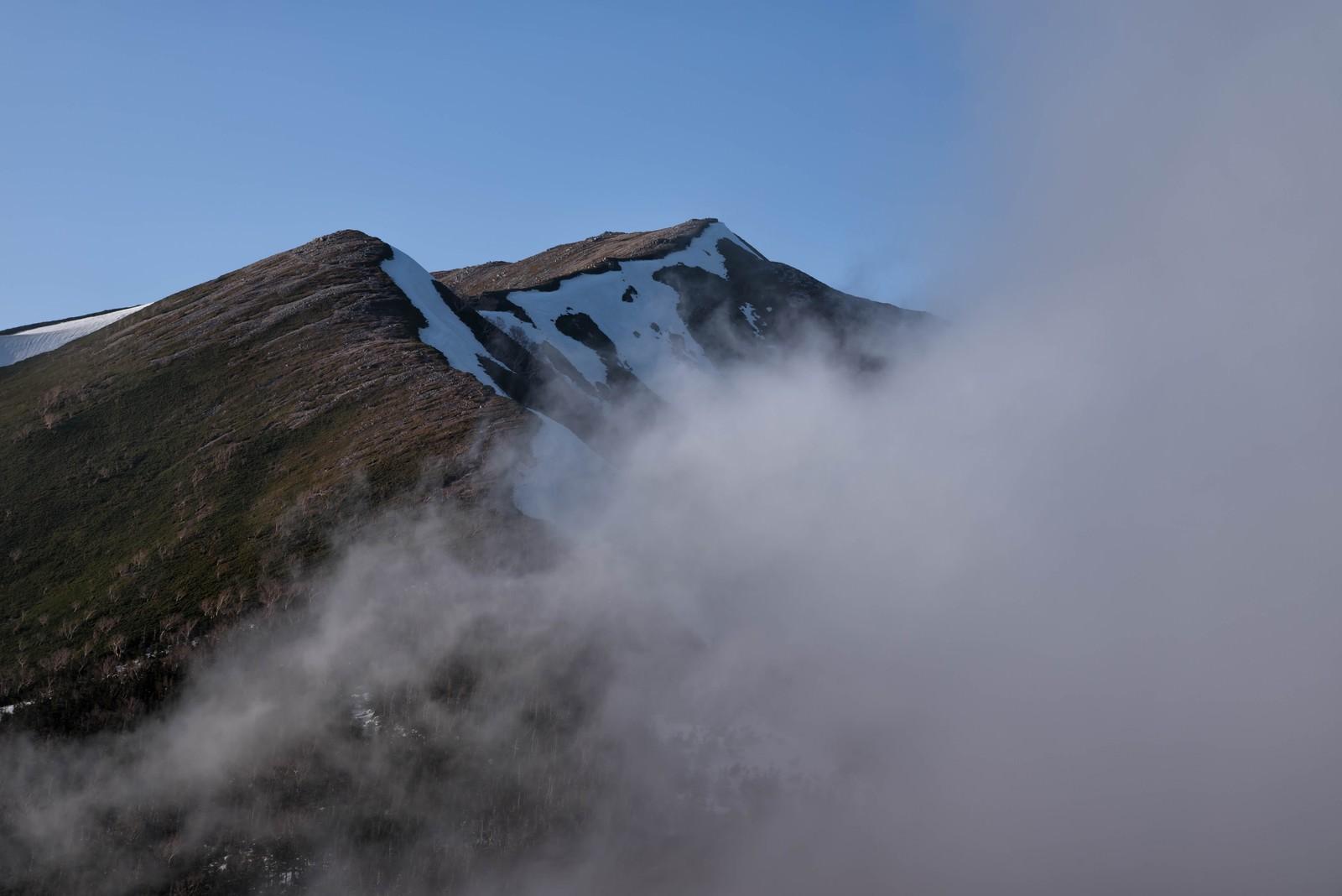 「雲に覆われる横通岳」の写真