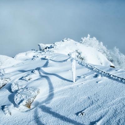 付着した氷や雪がエビの尻尾状になったロープと伸びる影の写真