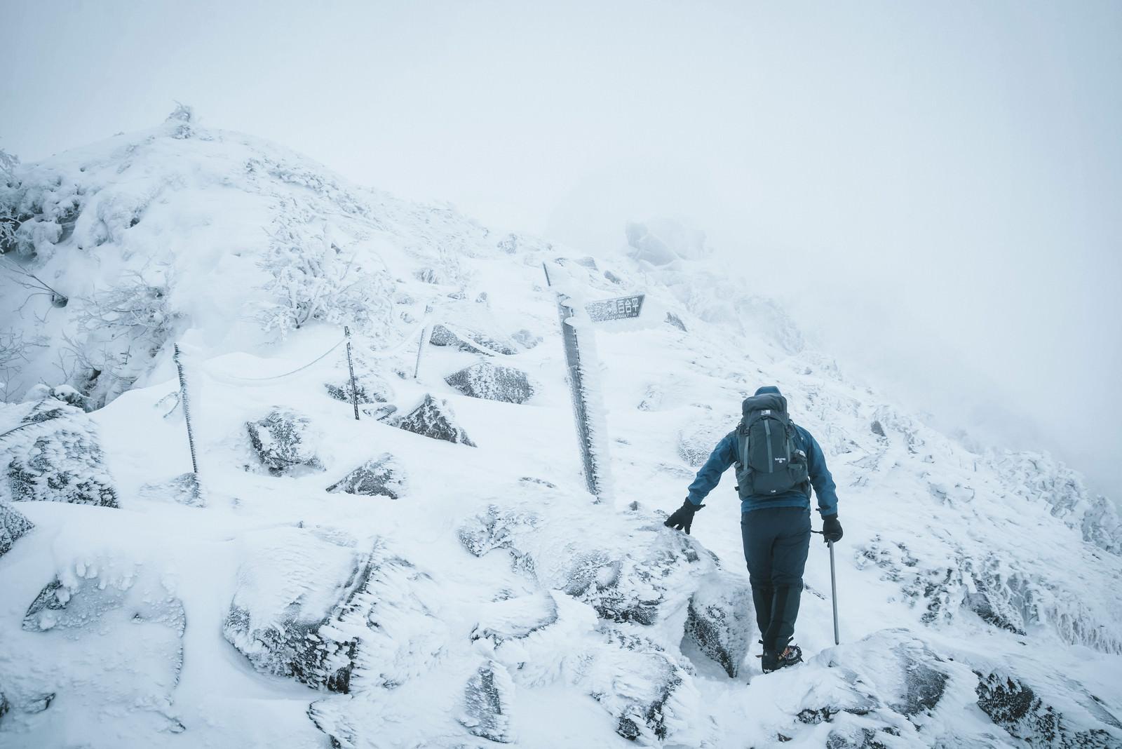 「冬山の標識と登山者」の写真
