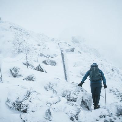 冬山の標識と登山者の写真