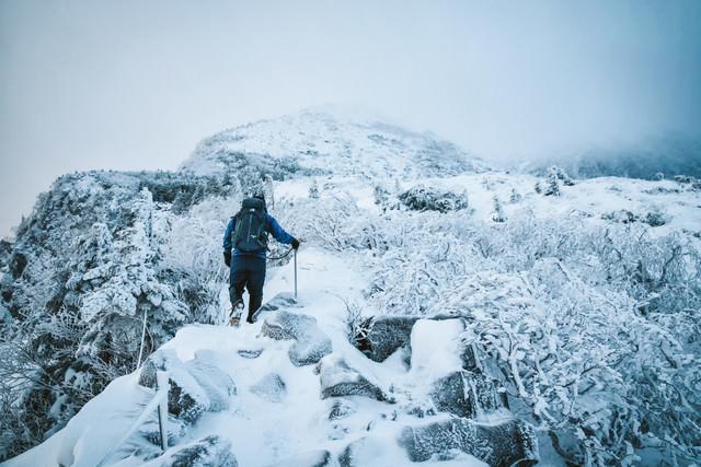 厳冬の登山道で道狭き場所を歩く登山者の写真