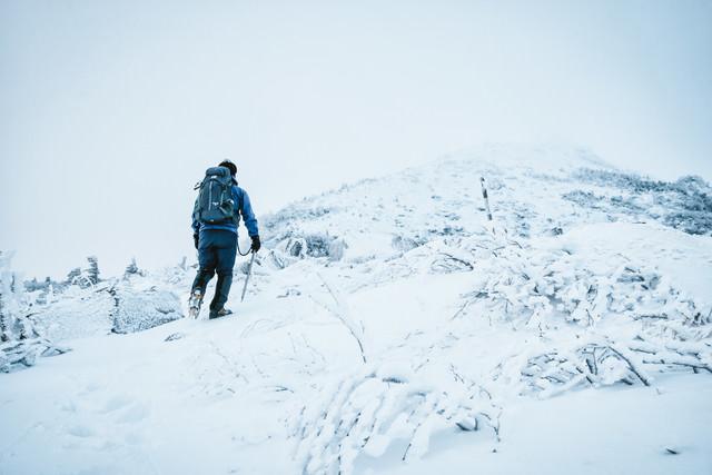 ピッケルとアイゼンを装備して挑む雪山の写真