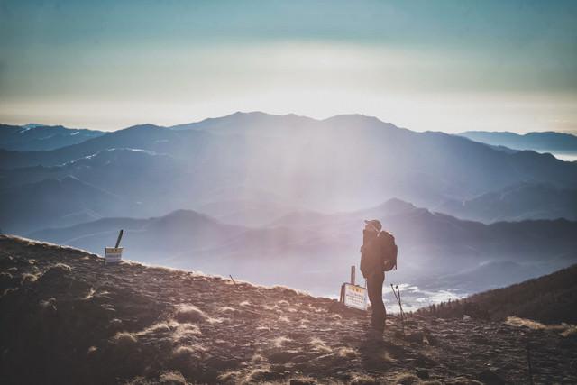 山頂を仰ぎ見る登山者と霞む山々の写真