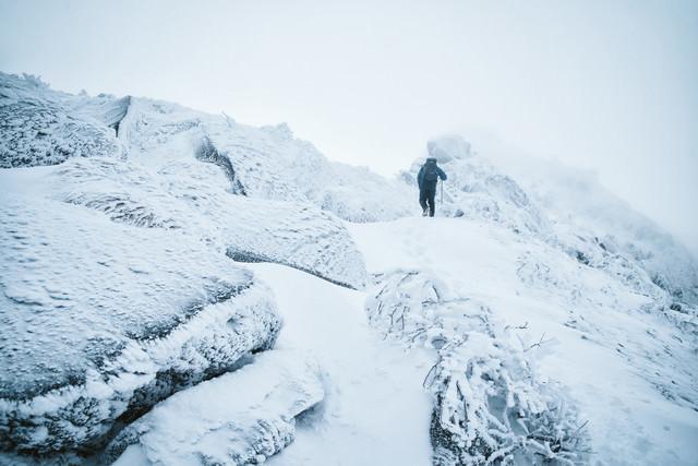 立ち込めるガスの中を登る登山者の写真