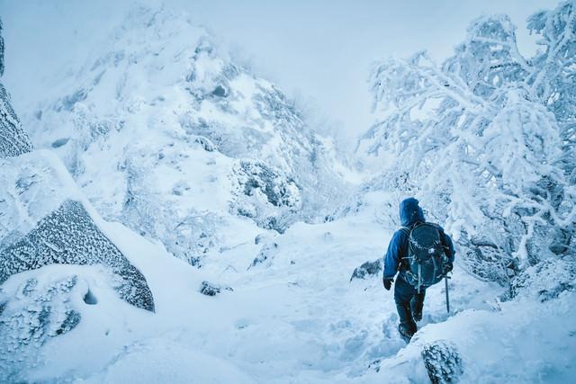 吹雪く雪山を下山する登山者の写真