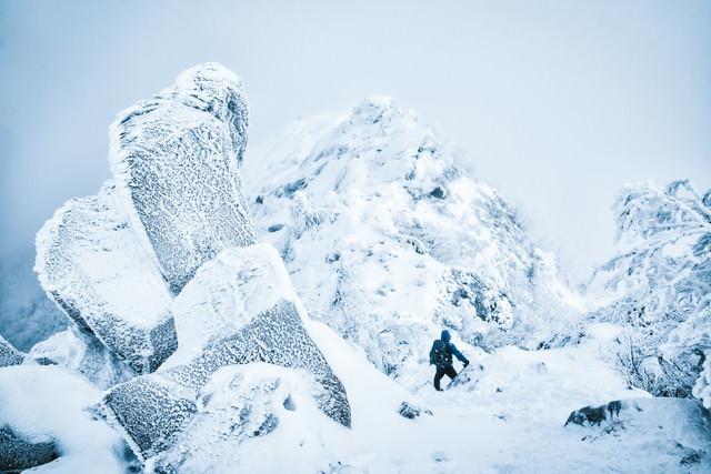 吹雪く天狗岳の稜線と登山者の写真