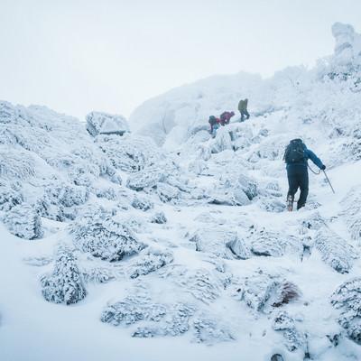 悪天候の雪山に挑む登山者達の写真