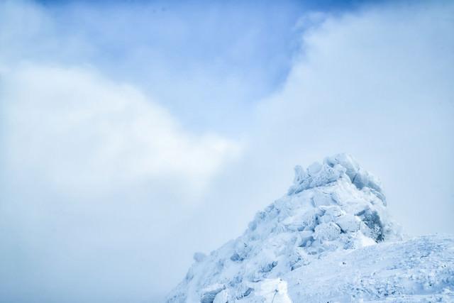 雲の切れ間と積雪した岩峰の写真