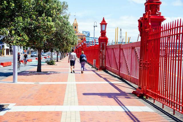オークランド港の遊歩道を歩くカップルの写真