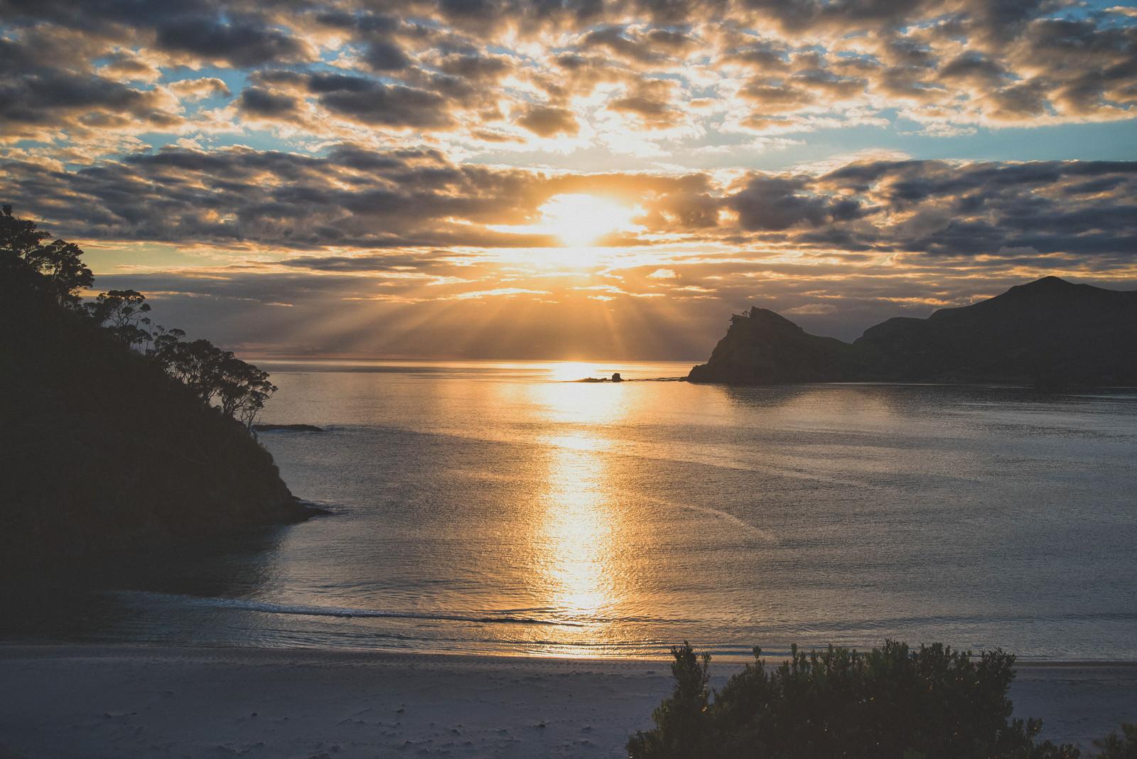 「グレートバリア島の海に伸びる朝日のレイライン(ニュージーランド)」の写真