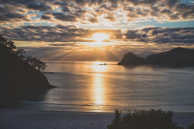 グレートバリア島の海に伸びる朝日のレイライン(ニュージーランド)の写真