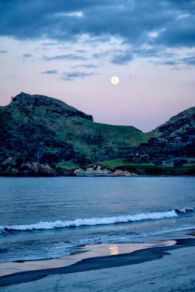 グレートバリア島の浜辺に打ち寄せる波と満月(ニュージーランド)の写真