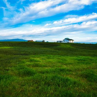 ニュージーランド郊外の広大な草原の中にある家の写真
