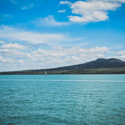 ハウラキ湾に浮かぶヨットと島(ニュージーランド)の写真