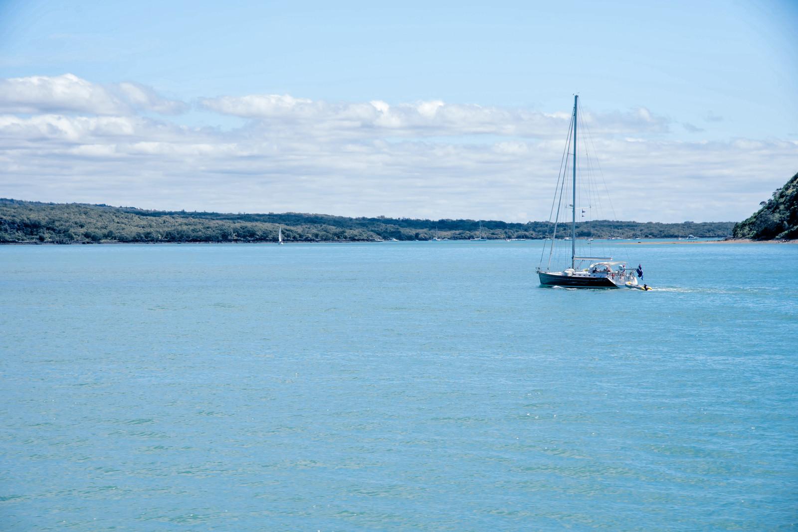 「ハウラキ湾に浮かぶ帆を立てていないヨット(ニュージーランド)」の写真