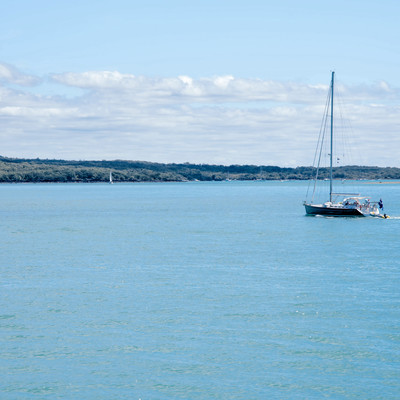 ハウラキ湾に浮かぶ帆を立てていないヨット(ニュージーランド)の写真