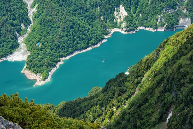 針ノ木岳から見下ろす黒部ダムと遊覧船の写真
