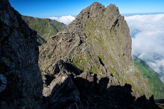 絶壁の岩場を登る登山者の写真