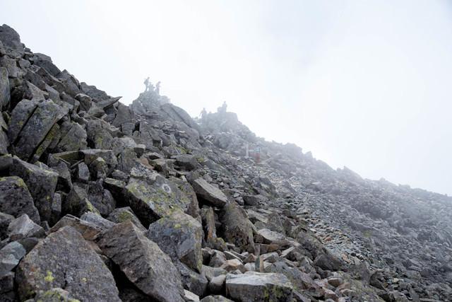 霧のジャンダルムと登山者(奥穂高岳山頂)の写真
