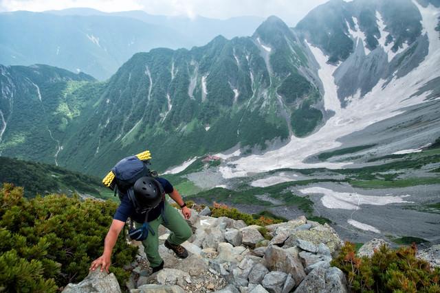 北穂高岳南陵の岩場(崖沿い)を登る登山者の写真