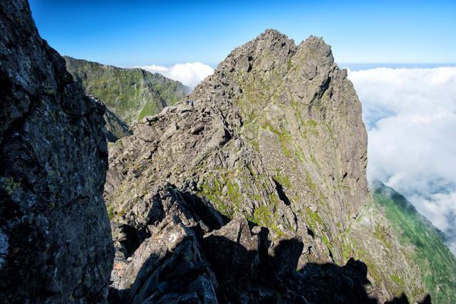 北穂高岳山頂下の難路に挑む登山者の写真