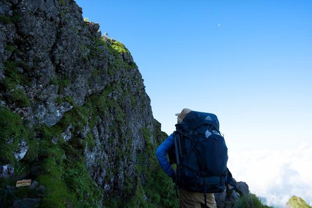 横岳の岩場を見上げる登山者(八ヶ岳)の写真